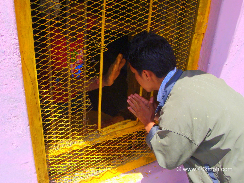 Man Applying Sandalwood Saffron Paste on Devotee's Forehead